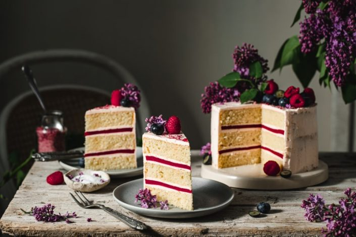 A pink layer cake with berries and lillac flowers.