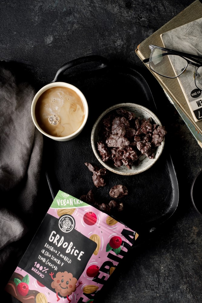 A bag of chocolate clusters from Teta Frida and coffee on black backdrop drop